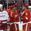 Photo - Detroit Red Wings left wing Drew Miller, center left, is congratulated by teammates after scoring during the second period of an NHL hockey game against the Washington Capitals in Detroit, Friday, Jan. 31, 2014. (AP Photo/Carlos Osorio)