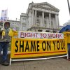 FILE - In this Nov. 22, 2011 file photo, Joe Lubbers, left, and Rick McKee display a sign in front of the Statehouse before start of Organization Day in Indianapolis. Union members rallied at the Statehouse ahead of a 2012 session that was to be dominated by