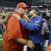 Photo - Kansas City Chiefs head coach Andy Reid, left, and Indianapolis Colts head coach Chuck Pagano meet on the field after an NFL wild-card playoff football game Saturday, Jan. 4, 2014, in Indianapolis. Indianapolis defeated Kansas City 45-44. (AP Photo/Michael Conroy)