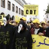 Moroccan members of the CDT labor union march behind activists dressed in fright masks carrying the labels