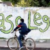 In this Nov. 15, 2012 file photo, young man rides a bicycle past a graffiti that reads in Spanish;