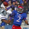 Photo - FILE - In this Nov. 30, 2013 file photo, Kansas quarterback Montell Cozart (2) passes over Kansas State linebacker Tre Walker (50) during the first half of an NCAA college football game in Lawrence, Kan. Cozart has won the starting job at Kansas, beating out Jake Heaps and T.J. Millweard after a strong spring game. (AP Photo/Orlin Wagner, File)