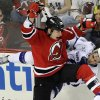 New Jersey Devils\' Cam Janssen (25) checks Tampa Bay Lightning\'s Cory Conacher during the second period of an NHL hockey game Tuesday, March 5, 2013, in Newark, N.J. (AP Photo/Bill Kostroun)