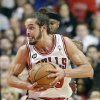 Photo - Chicago Bulls center Joakim Noah (13) works with the ball against Sacramento Kings forward Reggie Evans during the first half of an NBA basketball game in Chicago on Saturday, March 15, 2014. (AP Photo/Nam Y. Huh)