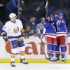 New York Rangers\' Chris Kreider, right, celebrates after teammate J.T. Miller, center, scored a goal while New York Islanders\' Brian Strait skates past during the first period of the NHL hockey game in New York, Thursday, Feb. 7, 2013. (AP Photo/Seth Wenig)