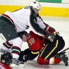 Minnesota Wild\'s Mikko Koivu, left, of Finland, pulls Calgary Flames\' Matt Stajan to the ice during the second period of their NHL hockey game, Monday, Feb. 11, 2013, in Calgary, Alberta. (AP Photo/The Canadian Press, Jeff McIntosh)