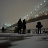 Visitors stop on the waterfront in Brooklyn to photograph the Brooklyn Bridge during a winter storm in New York, Thursday, Jan. 2, 2014. The storm is expected to bring snow, stiff winds and punishing cold into the Northeast. (AP Photo/Peter Morgan)