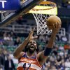 Photo - Washington Wizards' Nene (42) lays the ball up as Utah Jazz's Paul Millsap (24) defends during the first quarter of an NBA basketball game, Wednesday, Jan. 23, 2013, in Salt Lake City. (AP Photo/Rick Bowmer)