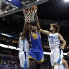 Photo - Golden State Warriors forward Harrison Barnes (40) dunks between New Orleans Hornets forward Darius Miller, left, and center Robin Lopez (15) in the first half of an NBA basketball game in New Orleans, Monday, March 18, 2013. (AP Photo/Gerald Herbert)