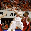 OSU\'s Keiton Page draws the defense as he dishes off during the college basketball game between Oklahoma State University and Nebraska at Gallagher-Iba Arena in Stillwater Saturday, March 6, 2010. Photo by Doug Hoke, The Oklahoman ORG XMIT: KOD