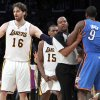 Photo -   Los Angeles Lakers' Pau Gasol (16), of Spain, stands between an official and Oklahoma City Thunder player after Lakers' Metta World Peace (15) was called for a double flagrant foul and ejected from the game in the first half of an NBA basketball game, Sunday, April 22, 2012, in Los Angeles. (AP Photo/Reed Saxon)