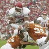 Photo - DALLAS, Saturday,10/11/2003: University of Oklahoma vs. University  of Texas college football at Cotton Bowl.   OU's Renaldo Works leaps over UT Reed Boyd (45) and Brian Robinson. Staff photo by Jim Beckel.