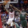 Photo - Houston Rockets guard James Harden (13) drives past Milwaukee Bucks guard Monta Ellis (11) and forward Ekpe Udoh (13) during the first half of an NBA basketball game, Wednesday, Feb. 27, 2013 in Houston. (AP Photo/Bob Levey)