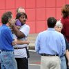 """Photo - FedEx Employee Lisa Aiken, wearing bandana, is embraced by a co-worker as other FedEx employees gather at a skating rink following a shooting at a FedEx facility in Kennesaw, Ga., on Tuesday, April 29, 2014.  A shooter described as being armed with an assault rifle and having bullets strapped across his chest opened fire Tuesday morning at a FedEx station outside Atlanta, wounding at least six people before police found the suspect dead from an apparent self-inflicted gunshot. """"He had bullets strapped across his chest like Rambo, a huge assault rifle and he had a knife,"""" Aiken said.  (AP Photo/Atlanta Journal-Constitution, Brant Sanderlin)"""