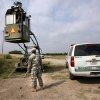 FILE - In this April 19, 2011, file photo, a member of the National Guard checks on his colleague inside a Border Patrol Skybox near the Hidalgo International Bridge in Hidalgo, Texas. Illegal immigration has slowed in recent years, with the Border Patrol recently recording the fewest arrests in almost 40 years. But many people worry that the Mexican border, the most popular crossing point for newly arriving illegal immigrants, still isn't secure more than a decade after the Sept. 11, 2001, terrorist attacks. (AP Photo/Delcia Lopez, File)