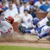 Photo - St. Louis Cardinals' Jon Jay, left, scores past Chicago Cubs catcher Welington Castillo during the seventh inning of a baseball game on Saturday, July 26, 2014, in Chicago. (AP Photo/Andrew A. Nelles)