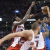 Photo - Orlando Magic's Tobias Harris, right, shoots over Toronto Raptors' Amir Johnson, left, Jonas Valanciunas, center, and Kyle Lowry during the first half of an NBA basketball game in Toronto, Sunday, Feb. 23, 2014. (AP Photo/The Canadian Press, Chris Young)