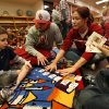 Baseball pitcher Cole Stevens, wearing a cap, and rowing athlete Ashley Lafollette use playing cards to teach math skills to Luca Perillo, 6, left, and Ryan Floyd, 6. PHOTOS BY STEVE SISNEY, THE OKLAHOMAN