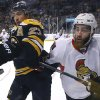 Photo - Boston Bruins center Chris Kelly (23) and Ottawa Senators defenseman Eric Gryba (62) compete for the puck along the boards during the second period of an NHL hockey game in Boston, Saturday, Feb. 8, 2014. (AP Photo/Elise Amendola)