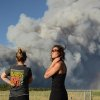 The Black Forest Fire burns northeast of Colorado Springs, Colo., Tuesday, June 11, 2013, as nearby residents Amy O\'Connor, left, and Nathalie Bartleson watch it creep toward the tree line. The fire consumed an estimated 7,500 acres, damaged 40-60 structures and forced the evacuation of thousands of people. (AP Photo/Bryan Oller)