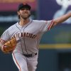 Photo - San Francisco Giants starting pitcher Madison Bumgarner works against the Colorado Rockies in the first inning of a baseball game in Denver on Tuesday, May 20, 2014. (AP Photo/David Zalubowski)