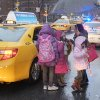 An unidentified woman arrives with her children by taxi at Public School 33, Wednesday, Jan. 16, 2013 in New York. More than 8,000 New York City school bus drivers and aides went on strike over job protection Wednesday morning, leaving some 152,000 students trying to find other ways to get to school. (AP Photo/Mark Lennihan)