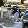 Norman Police carry equipment down the driveway of a home at 310 180th Avenue SE on Friday, October 29, 2010, in Little Axe Okla. where a woman and child were found dead on Thursday. Photo by Steve Sisney, The Oklahoman