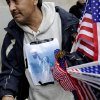 A poster showing the Statue of Liberty holding the head of Osama bin Laden is taped to Francisco Miranda\'s clothes as he sells flags at ground zero in New York, Monday, May 2, 2011. Joyous at the release of a decade\'s frustration, Americans streamed to the site of the World Trade Center, the gates of the White House and smaller but no less jubilant gatherings across the nation to celebrate the death of Osama bin Laden