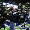 Photo - Seattle Seahawks' Richard Sherman celebrates with fans after after the NFL football NFC Championship game against the San Francisco 49ers Sunday, Jan. 19, 2014, in Seattle. The Seahawks won 23-17 to advance to Super Bowl XLVIII. (AP Photo/Elaine Thompson)