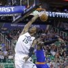 Photo - Utah Jazz's Derrick Favors (15) dunks the ball as New York Knicks' Iman Shumpert (21) defends in the first quarter during an NBA basketball game Monday, March 31, 2014, in Salt Lake City. (AP Photo/Rick Bowmer)