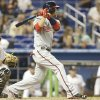 Photo - Washington Nationals' Bryce Harper hits a single during the eighth inning of a baseball game as Miami Marlins catcher Jarrod Saltalamacchia, left, looks on, Tuesday, April 15, 2014, in Miami. The Marlins defeated the Nationals 11-2. (AP Photo/Lynne Sladky)