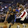 Photo - Orlando Magic shooting guard Arron Afflalo (4) drives past Washington Wizards forward Trevor Booker (35) in the first half of an NBA basketball game Monday, Dec. 2, 2013, in Washington. (AP Photo/Alex Brandon)