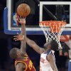 Photo - Cleveland Cavaliers' Kyrie Irving, left, puts up a shot as New York Knicks' Tim Hardaway Jr. defends during the first quarter of an NBA basketball game Thursday, Jan. 30, 2014, at Madison Square Garden in New York. (AP Photo/Bill Kostroun)