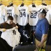 Photo - Phil Castinetti, of Boston, Mass., watches his son Cory, left, try on a New York Yankees jersey after watching a spring training baseball practice Tuesday, Feb. 18, 2014, in Tampa, Fla. (AP Photo/Charlie Neibergall)
