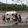 Relatives cross a river to bury their loved one, who died in a flash flood caused by Typhoon Bopha, Thursday, Dec. 6, 2012, in New Bataan township, Compostela Valley in southern Philippines. The powerful typhoon that washed away emergency shelters, a military camp and possibly entire families in the southern Philippines has killed hundreds of people with nearly 400 missing, authorities said Thursday. (AP Photo/Bullit Marquez)
