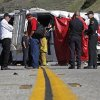 Investigators stand at the scene after a tour bus was lifted back onto the road Monday, Feb. 4, 2013, after it collided with two other vehicles and crashed Sunday, killing at least eight people and injuring 38, just north of Yucaipa, Calif. The bus was carrying a tour group from Tijuana, Mexico. (AP Photo/Reed Saxon)