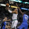 Boston Celtics forward Paul Pierce, center, threads between Orlando Magic forward Andrew Nicholson (44) and center Nikola Vucevic, left, on a drive to the basket during the first quarter of an NBA basketball game in Boston, Friday, Feb. 1, 2013. (AP Photo/Charles Krupa)