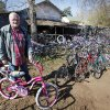 Photo - John Ballard poses with some of the bikes he repairs to give to children. Photo By Steve Gooch, The Oklahoman