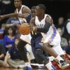 Oklahoma City Thunder guard Reggie Jackson, right, drives around New Orleans Pelicans\' Jrue Holiday, center, in the first quarter of an NBA basketball preseason game in Tulsa, Okla., Thursday, Oct. 17, 2013. (AP Photo/Sue Ogrocki) ORG XMIT: OKSO110