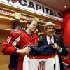 Photo - ** CORRECTS DATE to FEB. 6 ** Secretary of State John Kerry, right, poses for a photograph holding the team USA hockey jersey with Washington Capitals defenseman John Carlson, in the locker room before their game with the Winnipeg Jets, Thursday, Feb. 6, 2014, in Washington. Kerry was greeting players that have been selected for their country's Olympic hockey team. (AP Photo/Alex Brandon, Pool)