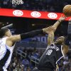 Photo - Brooklyn Nets' Marcus Thornton (10) takes a shot as he is fouled by Orlando Magic's Tobias Harris (12) during the first half of an NBA basketball game in Orlando, Fla., Wednesday, April 9, 2014. (AP Photo/John Raoux)