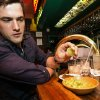 """Photo -   Dana Stolzner squeezes lime juice to his guacamole, while drinking his own """"Dana Margarita,"""" a coconut-based margarita cocktail, at the bar of El Coyote, a Mexican restaurant in Los Angeles.  AP Photos    -  AP"""