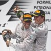 Photo - Mercedes driver Lewis Hamilton, left, of Britain and his teammate Nico Rosberg of Germany spray champagnes during the prize presentation on the podium after the Malaysian Formula One Grand Prix at Sepang International Circuit in Sepang, Malaysia, Sunday, March 30, 2014. Hamilton won the race while Rosberg finished in second. (AP Photo/Lai Seng Sin)