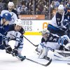 Photo - Winnipeg Jets goalie Ondrej Pavelec (31) makes a save as Toronto Maple Leafs forward James van Riemsdyk (21) and Jets defenseman Mark Stuart (5) battle for the loose puck during second-period NHL hockey game action in Toronto, Saturday, April 5, 2014. (AP Photo/The Canadian Press, Nathan Denette)