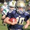 In this 2012 photo provided by Marycecelia Pla, her daughter, Caroline Pla, foreground, carries the ball during a Catholic Youth Organization league football game. The 11-year-old girl who\'s been playing football since kindergarten wants Philadelphia\'s Roman Catholic archdiocese to overturn a boys-only rule. (AP Photo/Pla Family)