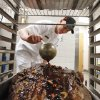 Food service specialist Sean Kennedy bastes a 50-pound roast. PHOTOS BY DAVID MCDANIEL, THE OKLAHOMAN