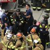 Photo - New York City firefighters emerge from a hatch in the sidewalk at 60th Street and Broadway after evacuating passengers from a subway train that derailed in the Queens borough of New York, Friday, May 2, 2014.  The express F train was bound for Manhattan and Brooklyn when it derailed at 10:40 a.m. about 1,200 feet (365 meters) south of the 65th Street station, according to the Metropolitan Transportation Authority. Dozens of firefighters and paramedics with stretchers converged on Broadway and 60th Street, where passengers calmly left the tunnel through the sidewalk opening. A few were treated on stretchers. (AP Photo/Julie Jacobson)