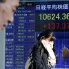People walk by an electronic stock board of a securities firm in Tokyo, Thursday, Jan. 24, 2013. Asian stock markets were mostly higher Thursday, supported by Congress averting a U.S. government default and a pickup in China\'s manufacturing in January. (AP Photo/Koji Sasahara)