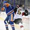 Photo - Ottawa Senators' Kyle Turris (7) is checked by Edmonton Oilers' Jeff Petry (2) during the first period of an NHL hockey game, Tuesday, March 4, 2014 in Edmonton, Alberta. (AP Photo/The Canadian Press, Jason Franson)