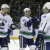 Photo - Vancouver Canucks defenseman Alexander Edler (23), from Sweden, right wing Jannik Hansen (36), from Denmark, and defenseman Kevin Bieksa (3) congratulate left wing Chris Higgins, hidden, after scoring during the second period of an NHL hockey game against the San Jose Sharks in San Jose, Calif., Monday, April 1, 2013. (AP Photo/Jeff Chiu)